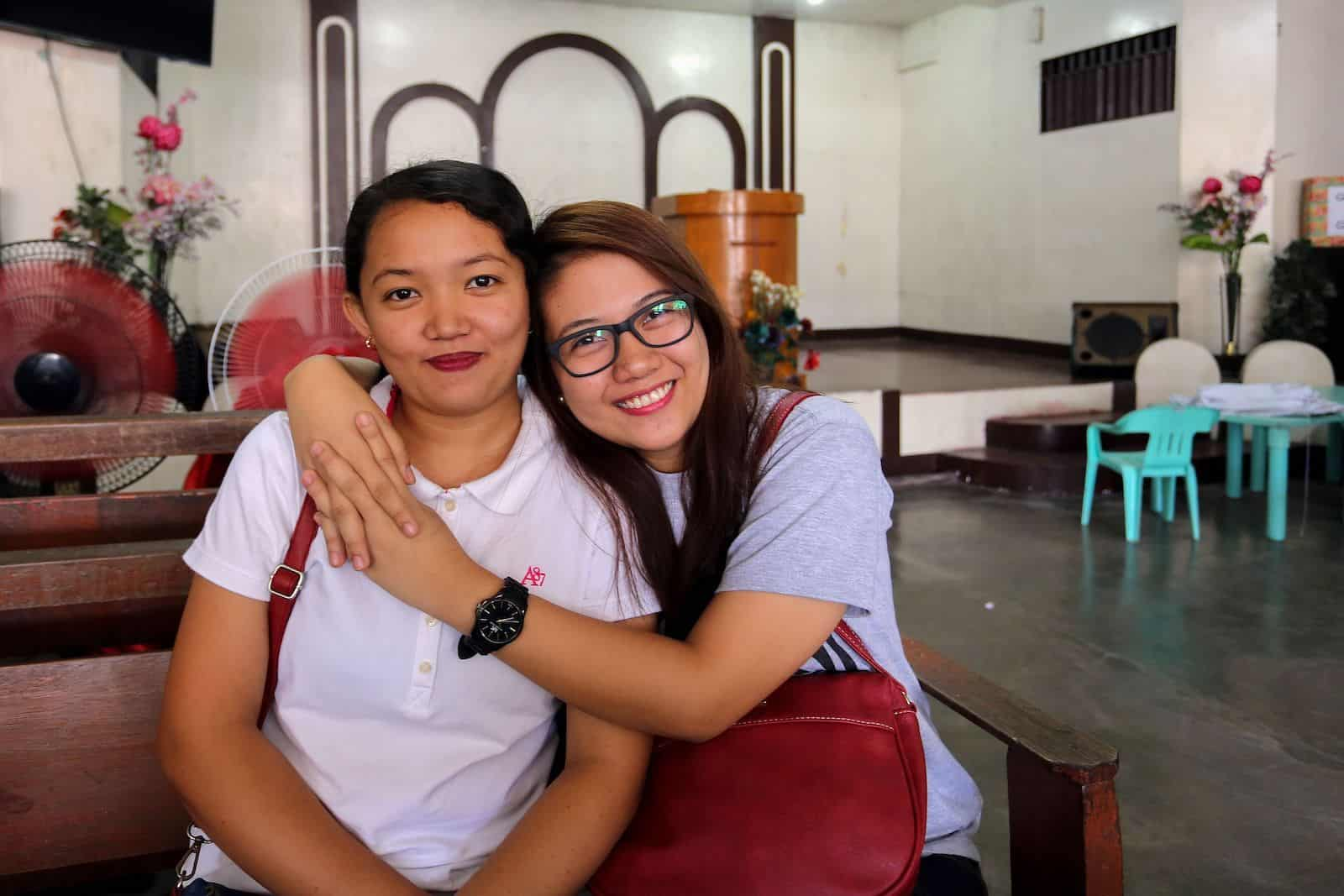 Two young women sit inside a church, one with her arms around the other, both smiling.