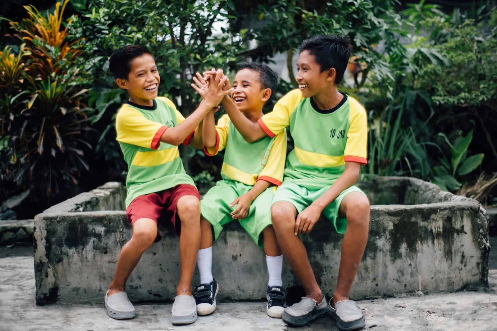 International Day of Friendship: Three boys sit outside wearing green and yellow sports uniforms, giving each other high fives.