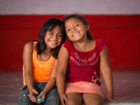Two young girls sit inside on a step in front of a red wall, smiling.