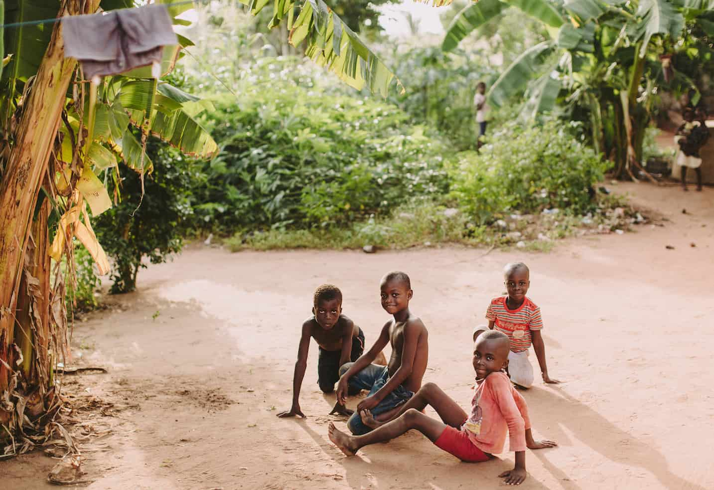 Children sit on the dirt ground, playing. There are palm trees in the background.