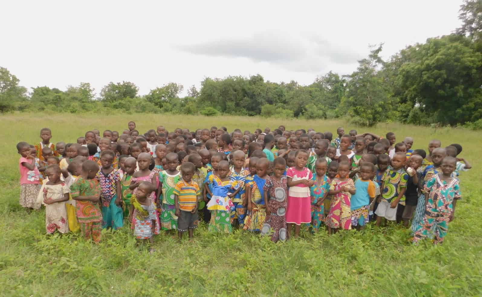 A large group of children in colorful clothes stand in a field in rural Togo.