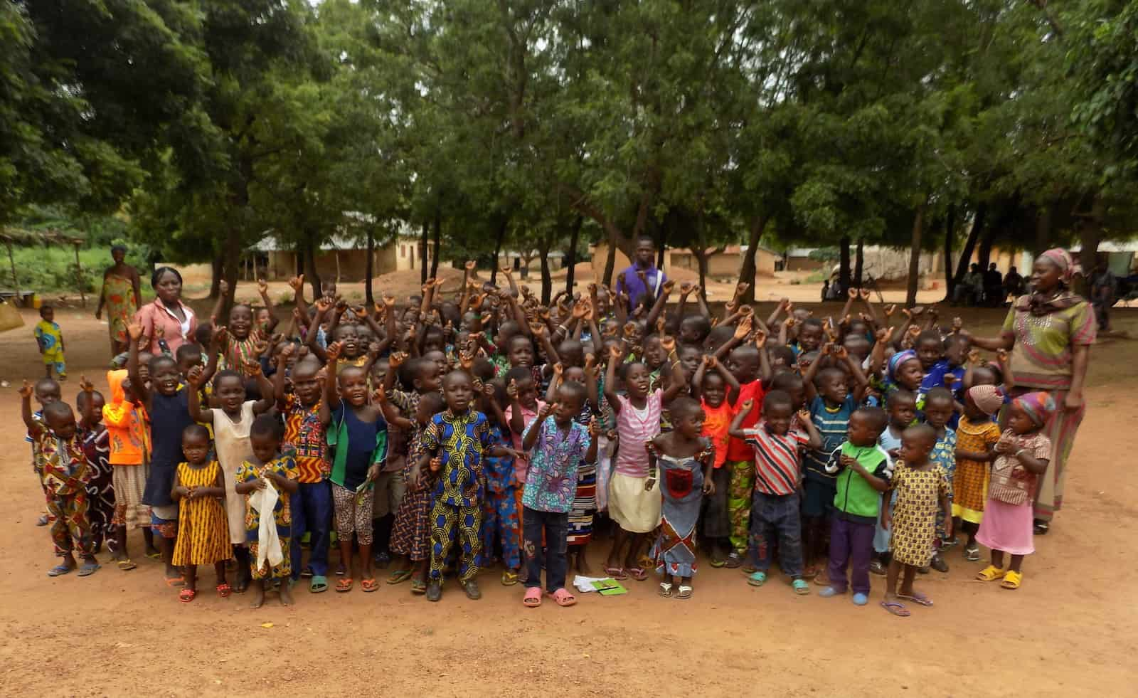 A large group of children in colorful clothes stands outside in front of a row of trees in rural Togo.