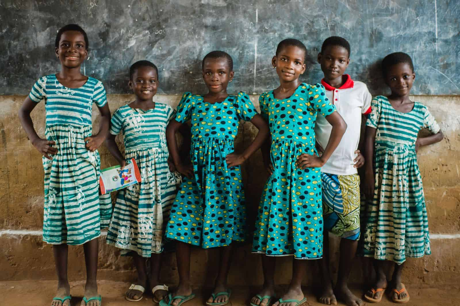 A group of girls in green patterned dresses stands in front of a chalkboard in a classroom, with hands on hips.