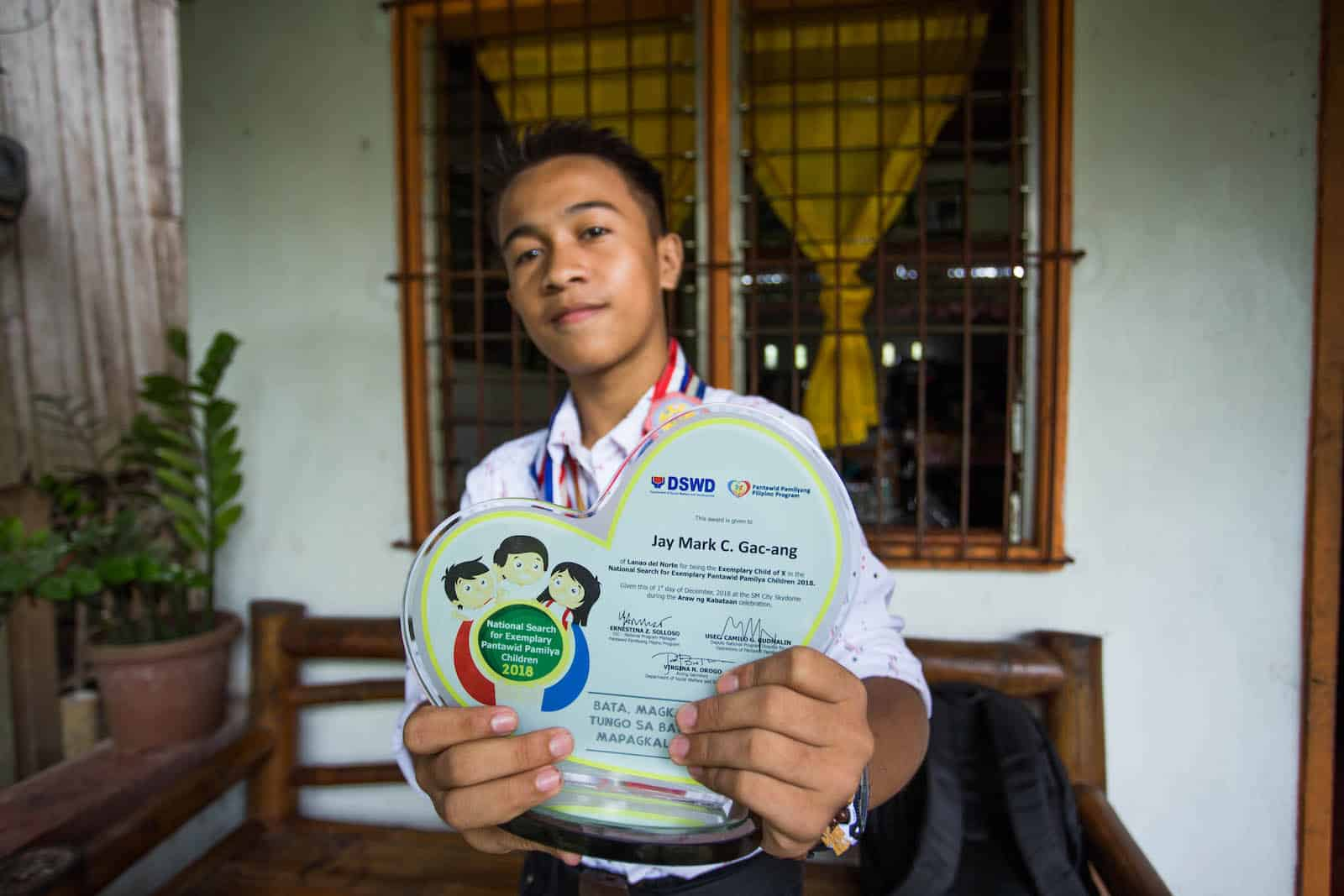 A teen boy stands outside a window, holding an award plaque for the Most Excellent Child in the Philippines.