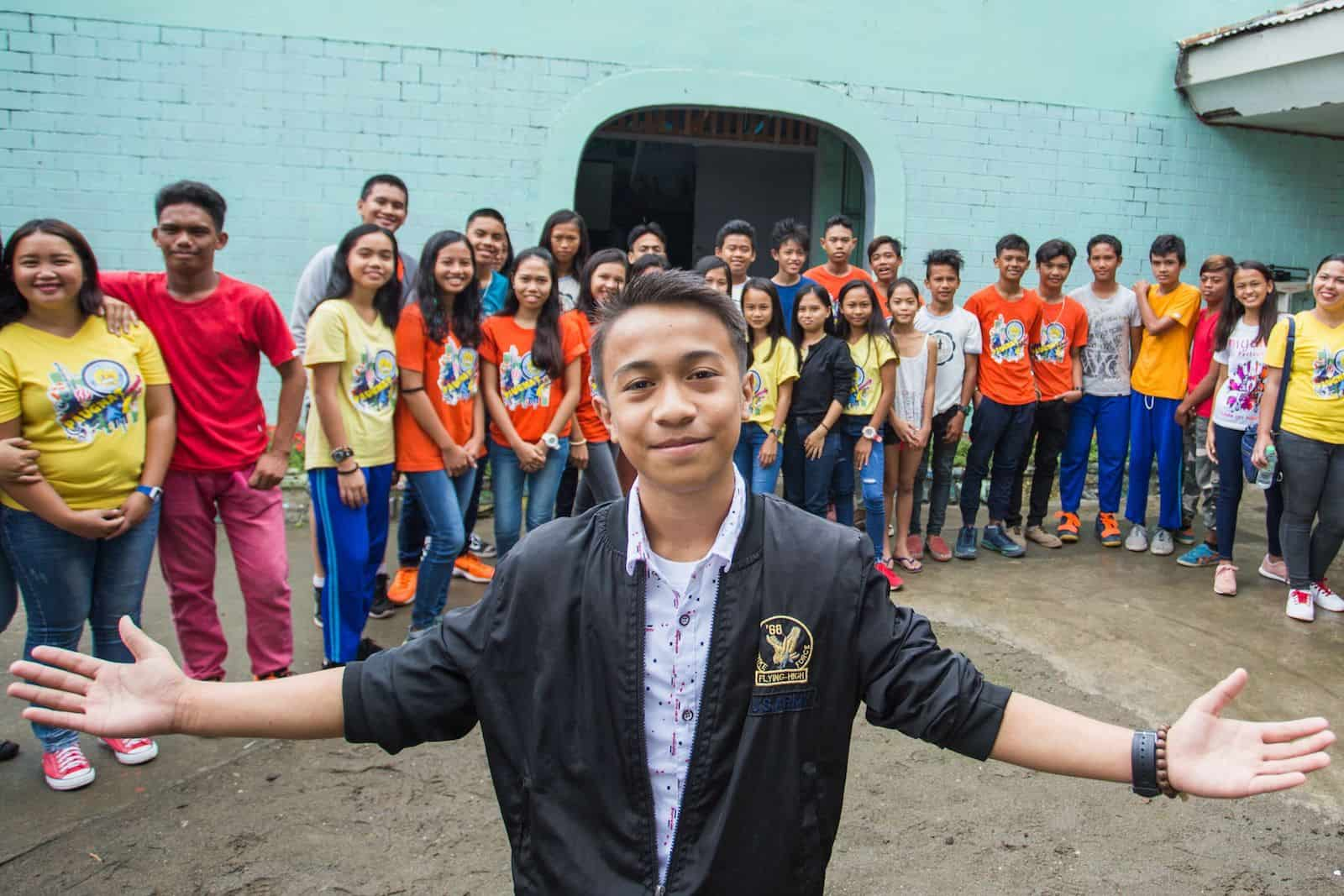 """A teen boy, the """"Most Excellent Child in the Philippines,"""" wearing a black jacket and white shirt holds his arms out to the side, smiling, standing in front of a large group of children in front of a church."""