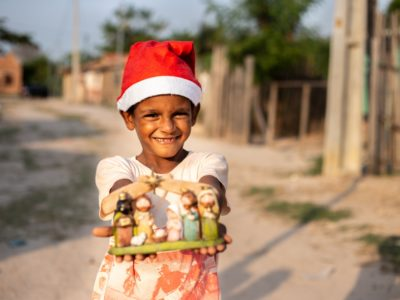 A boy wearing a red Santa cap holds out a small nativity set.