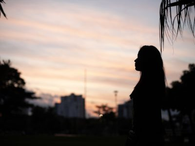 A young woman is silhouetted against a dusk sky.