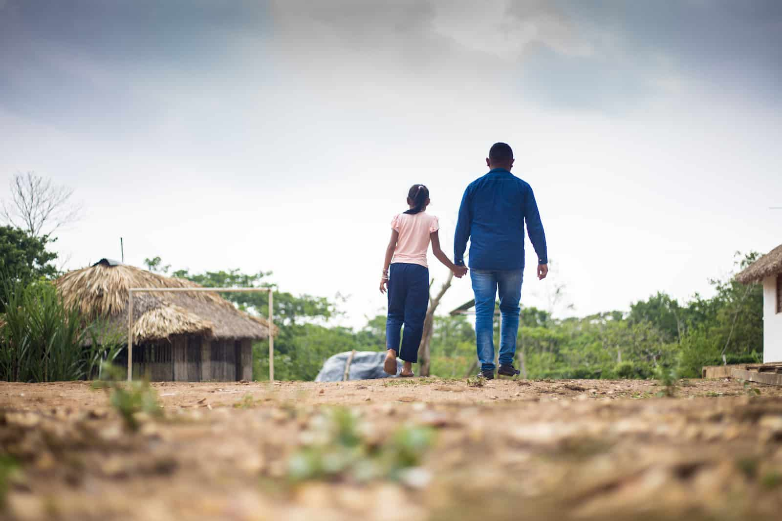 A man and girl walk down a dirt path, holding hands.