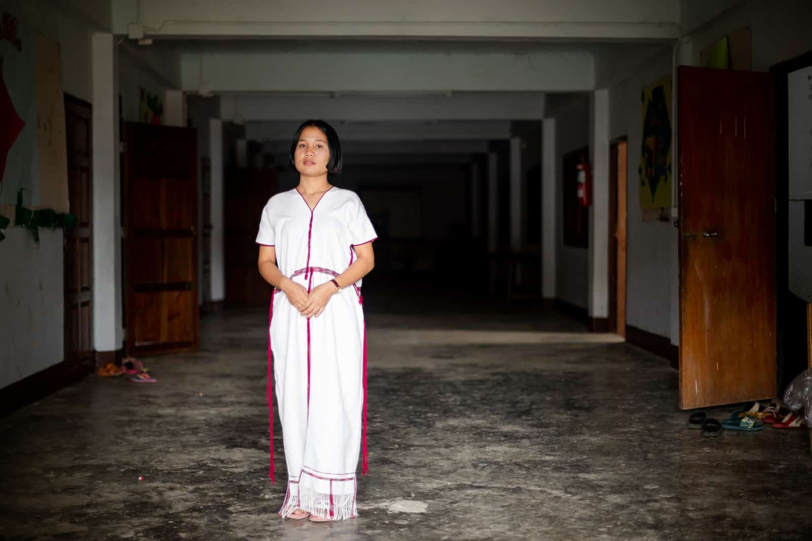 A girl in a long white dress stands in a long dark hallway.