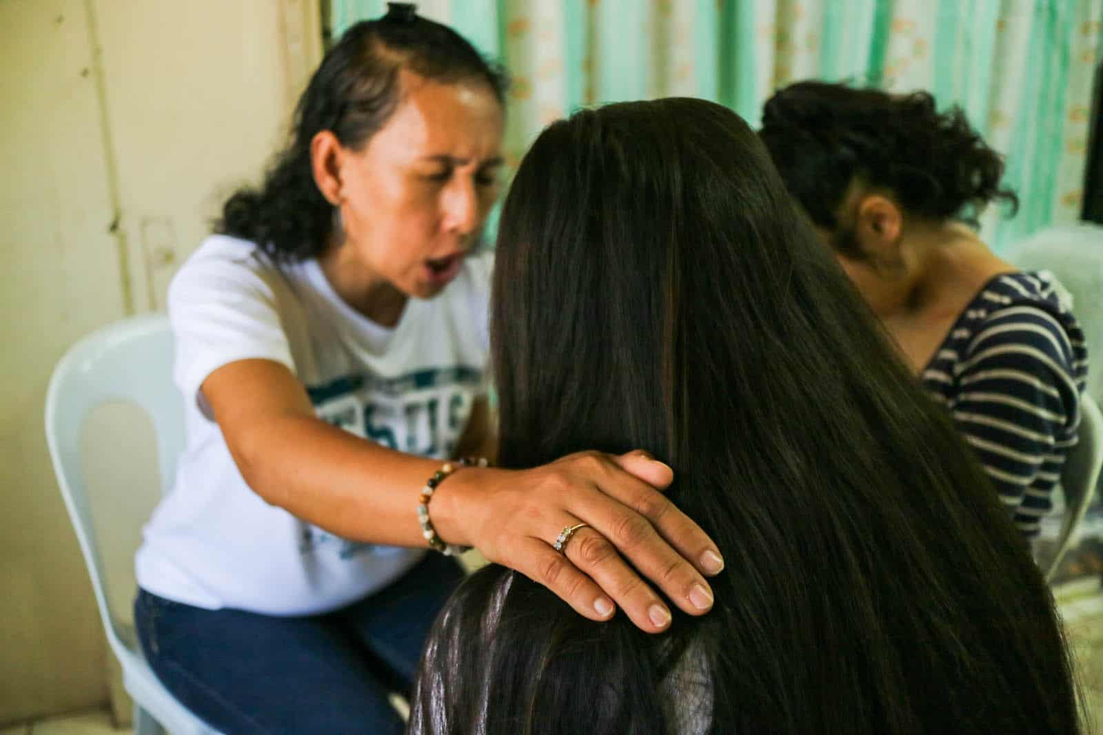A woman in a white T-shirt puts her hands on two girls, shown from behind, as she prays for survivors of child sexual abuse.