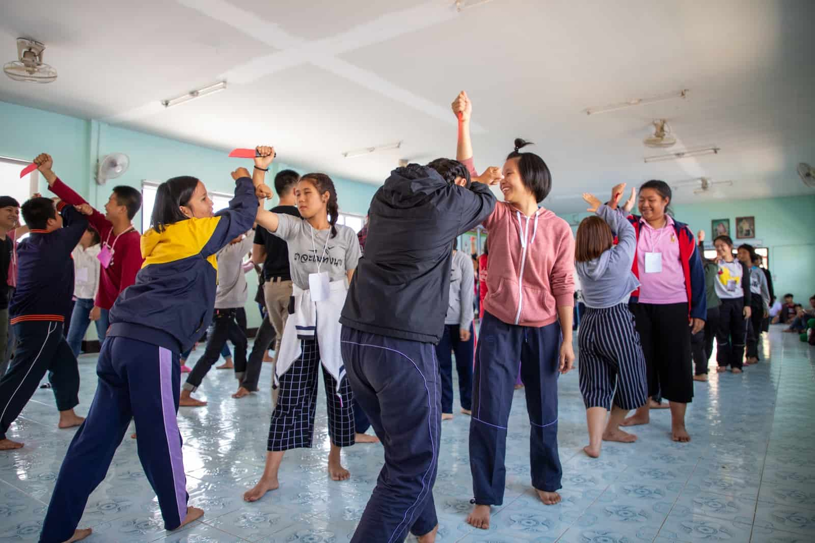 A group of girls stands in a classroom, practicing self-defense techniques to prevent child sexual abuse.