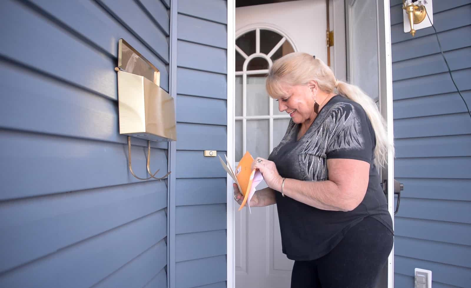 A woman in a black shirt checks the mail out of a box on the front porch of a house.