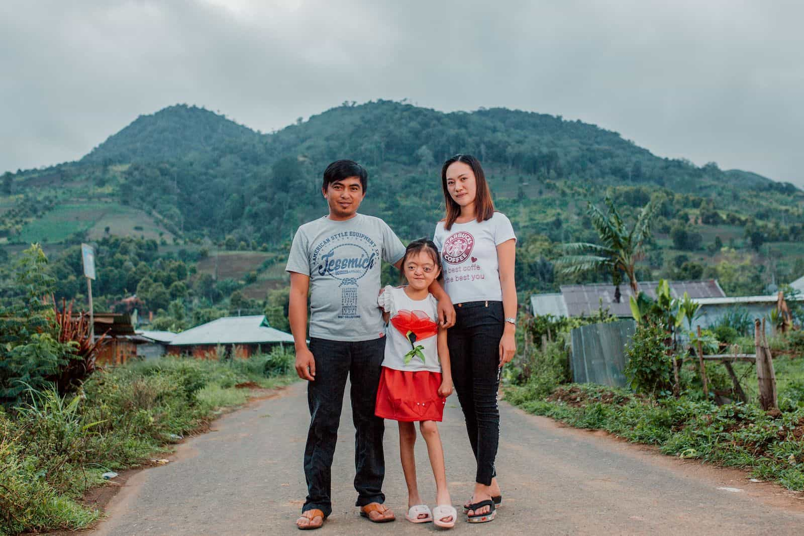 A photo of a girl with Apert Syndrome standing with two adults on a road in front of a mountain.