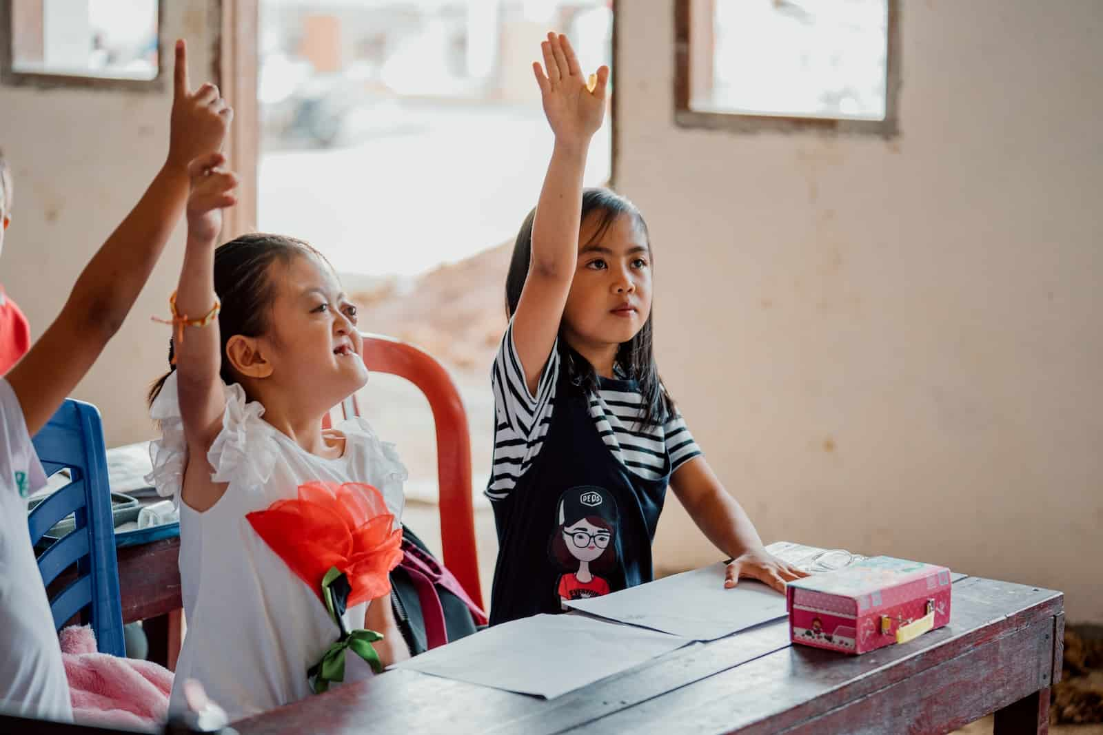 A photo of a girl with Apert Syndrome, raising her hand at school.