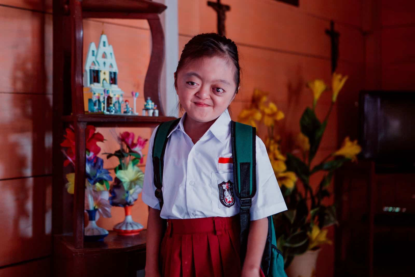 A photo of a girl with Apert Syndrome wearing a red and white school uniform and backpack, standing inside against a red wall.