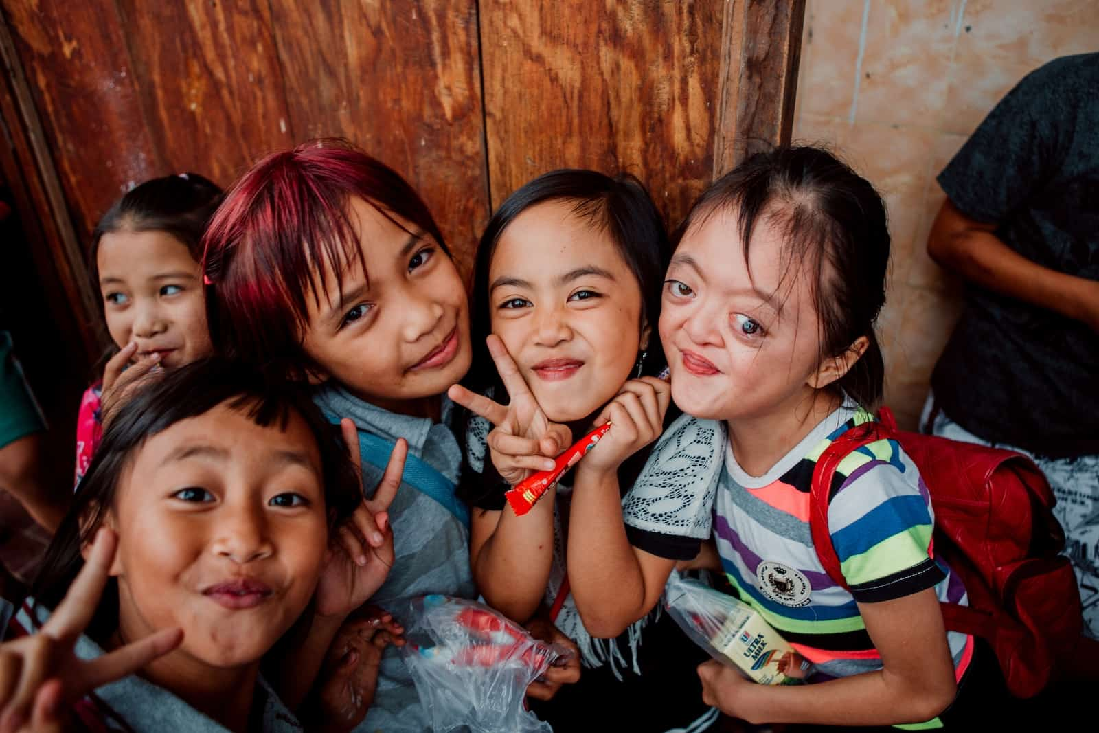 Four young girls, including one with Apert Syndrome, smile at the camera, making peace signs.