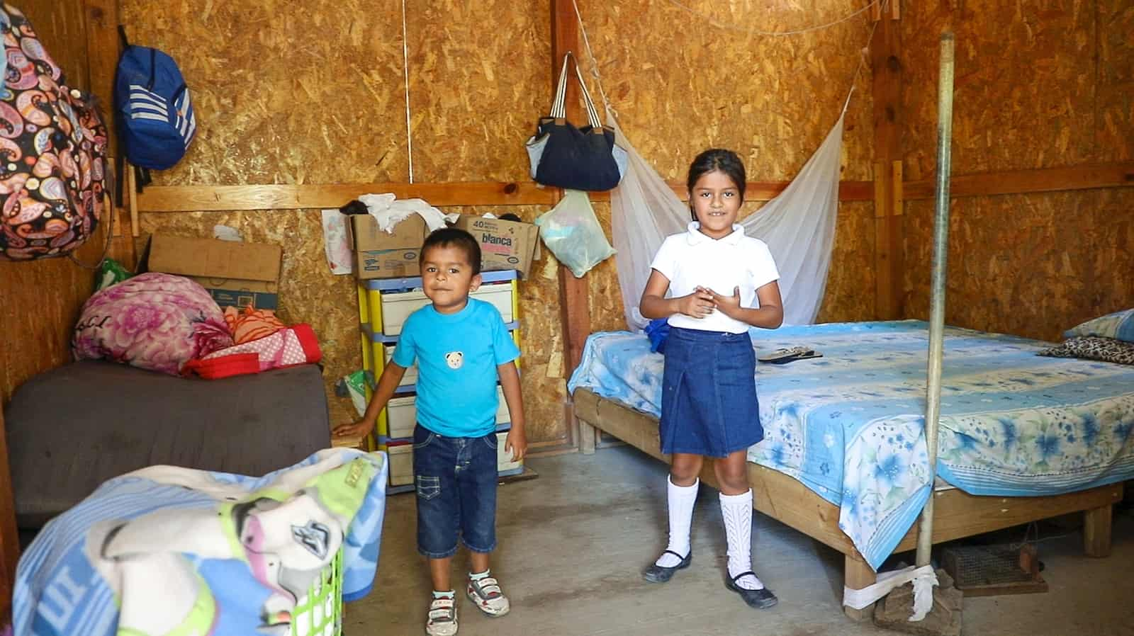 A boy and girl stand inside a home rebuilt after the Mexico earthquake next to their beds.