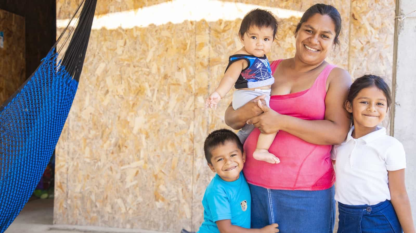 A woman in a pink tank-top holds a baby, with two young children standing at her sides, smiling.