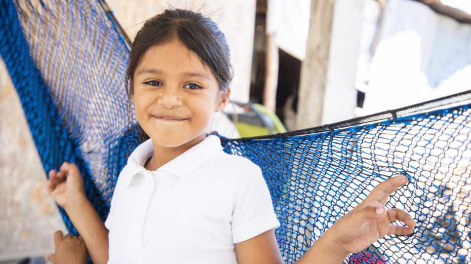 A girl in a white shirt stands in front of a blue hammock, smiling.