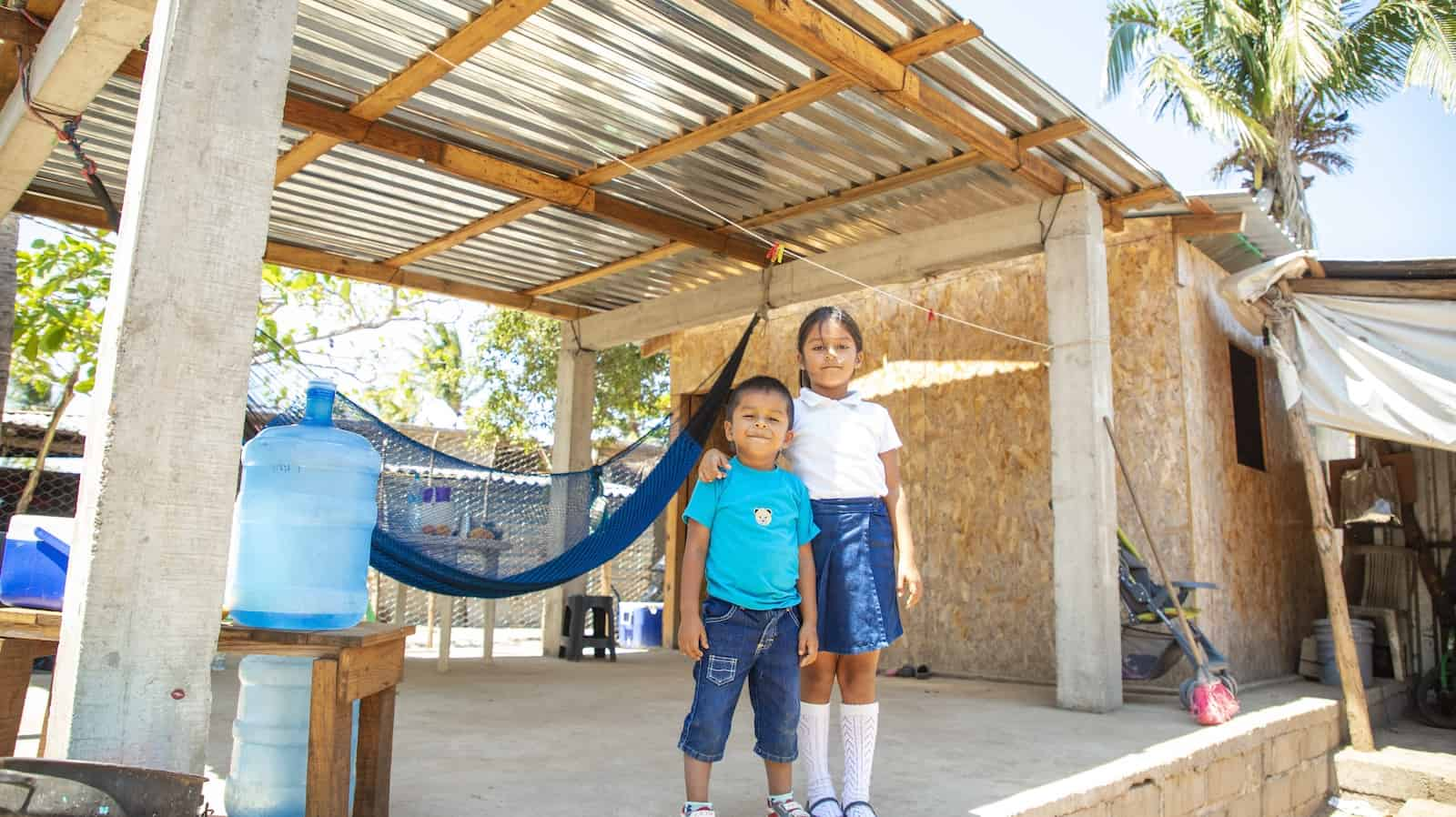 Two children stand in front of a home built after the Mexico earthquake made from plywood with a tin roof shelter in front of it.
