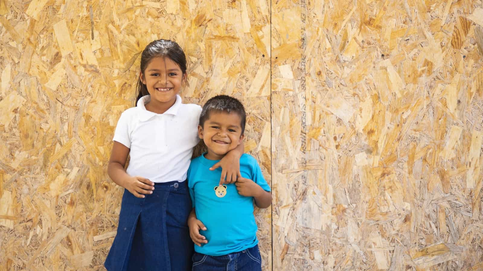 A boy and girl stand outside a home with their arms around each other, smiling.