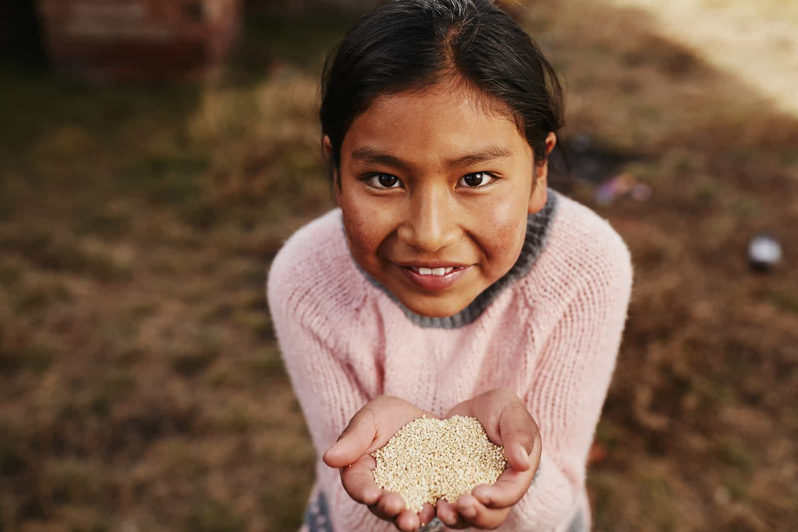 A girl in a pink sweater holds up a handful of seeds.