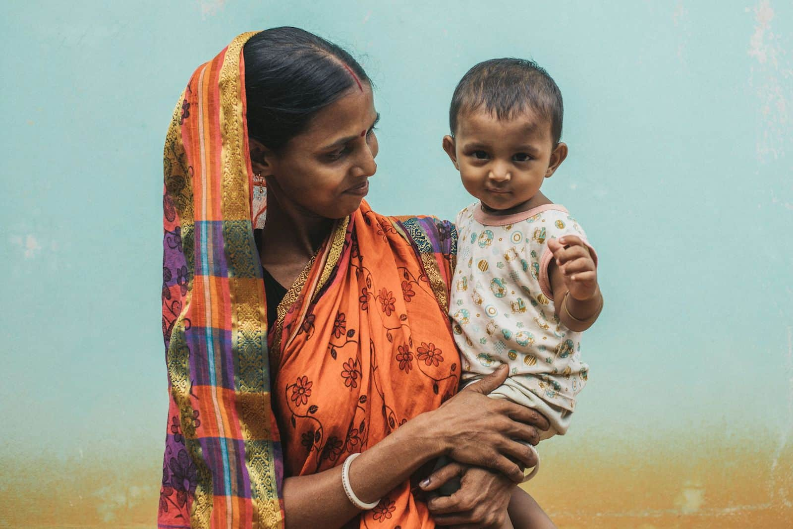 A woman in a sari holds a baby.