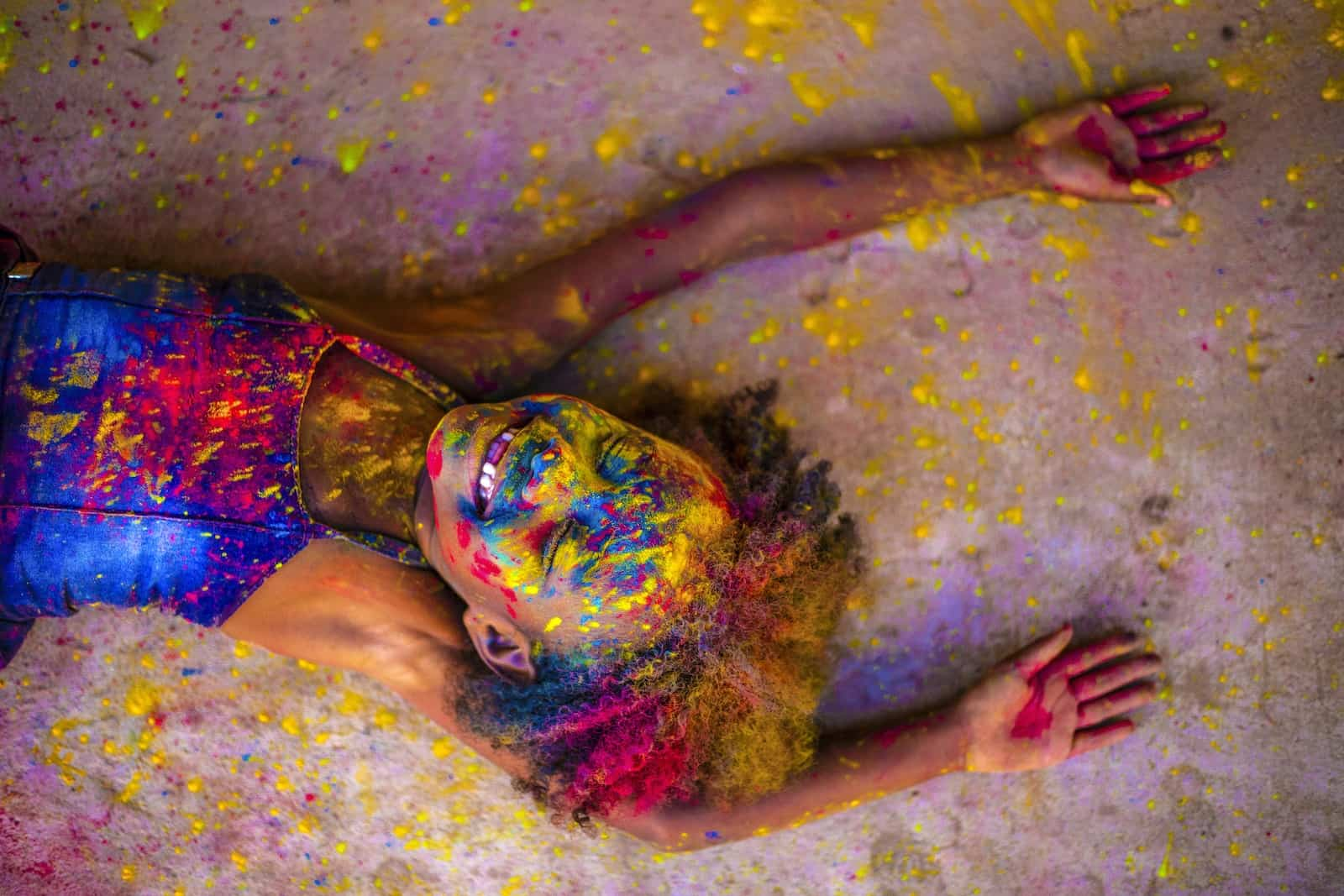 A girl covered in bright paint colors smiles, laying on the ground.