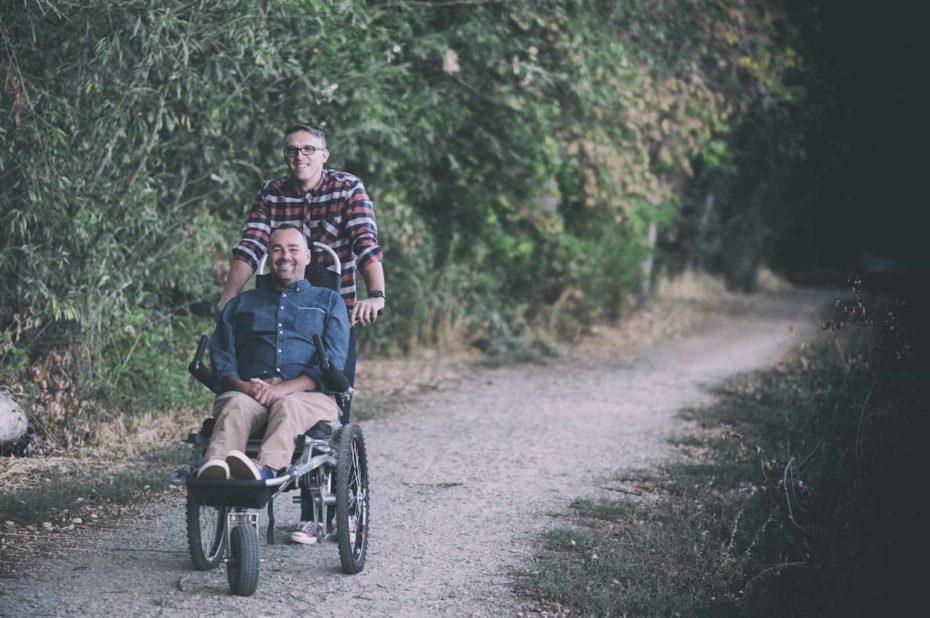 One man stands behind another man sitting in a wheelchair on a dirt path.