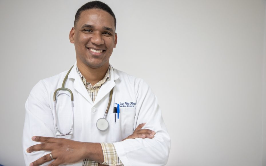 A man wearing a white doctor's coat and stethoscope around his neck smiles, arms crossed.