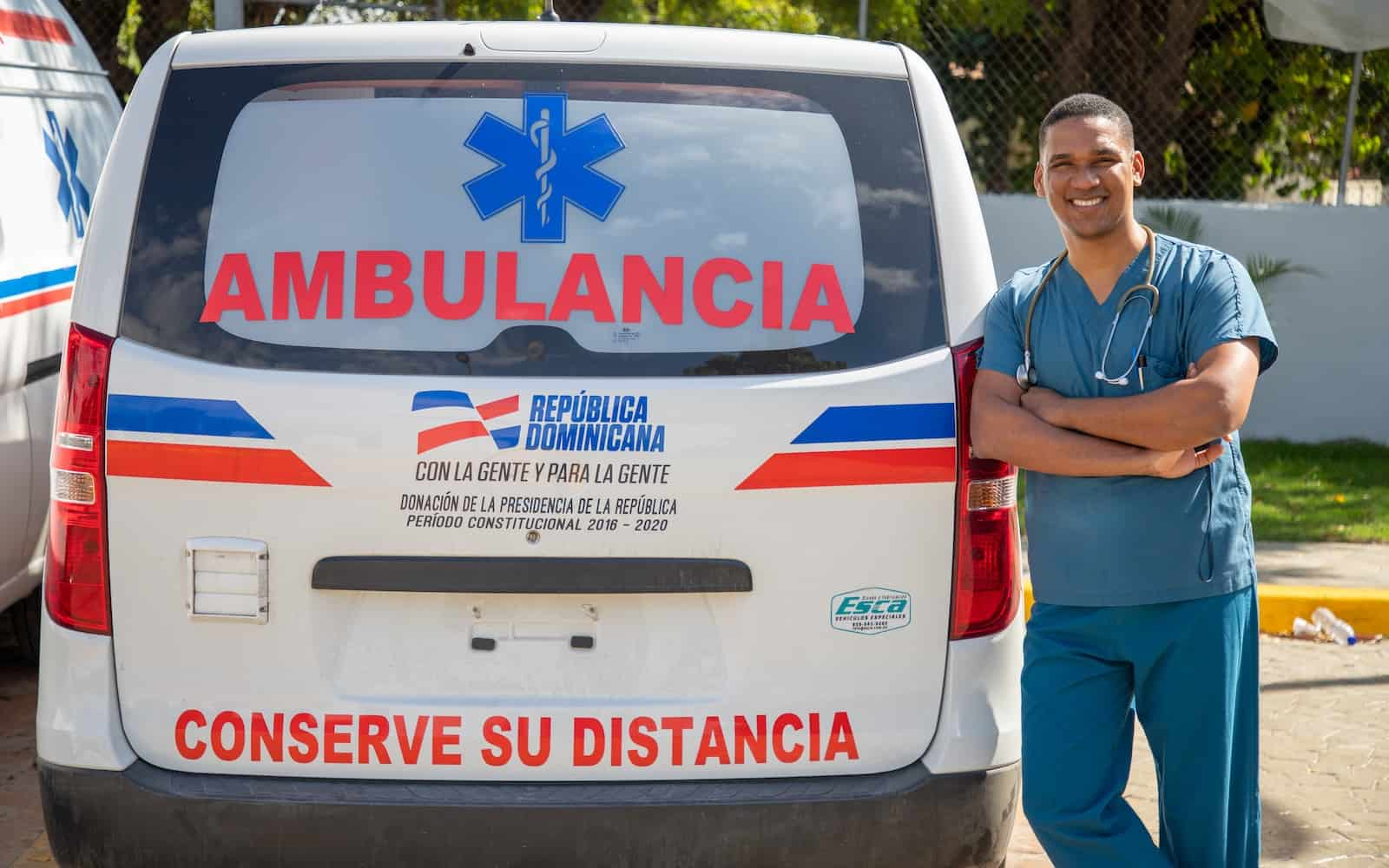 A man leans against an ambulance van.