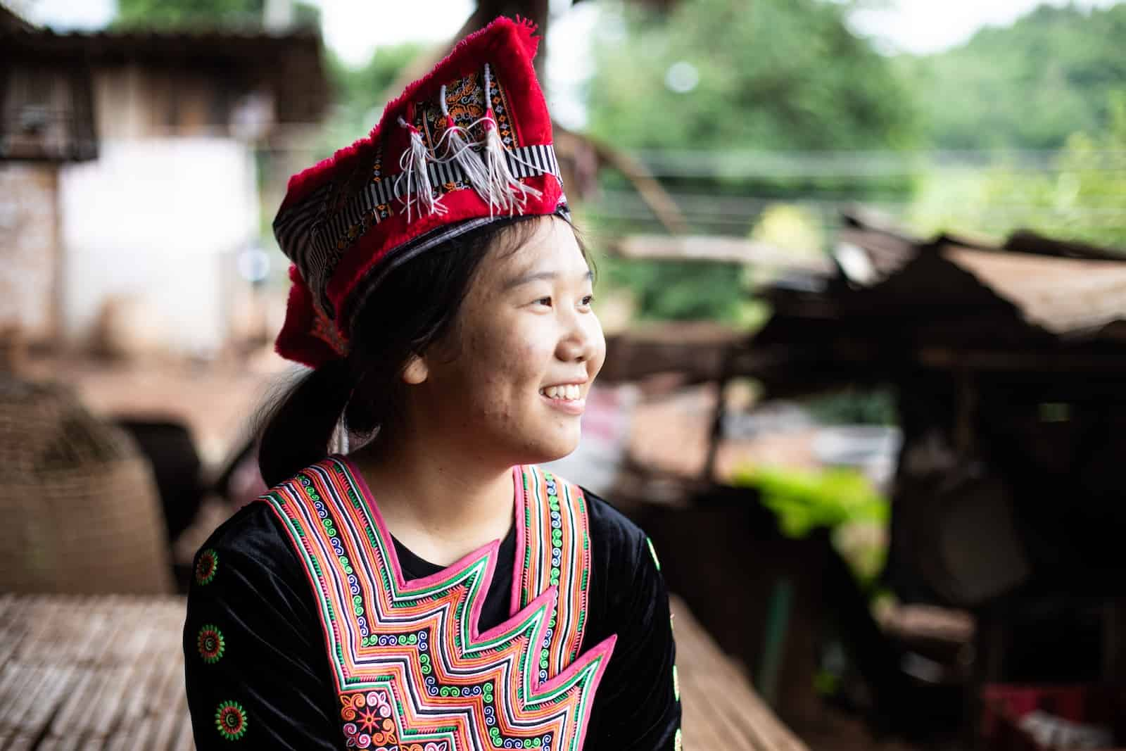 A girl wearing traditional Hmong clothing looks to the side, smiling.