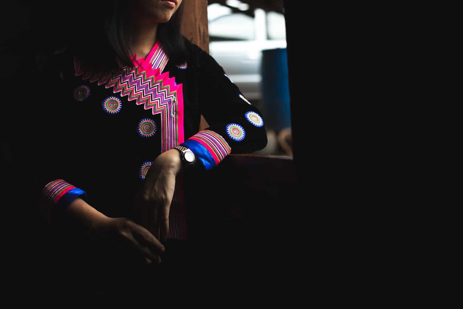 A girl wearing a colorful traditional Hmong outfit looks out the window.