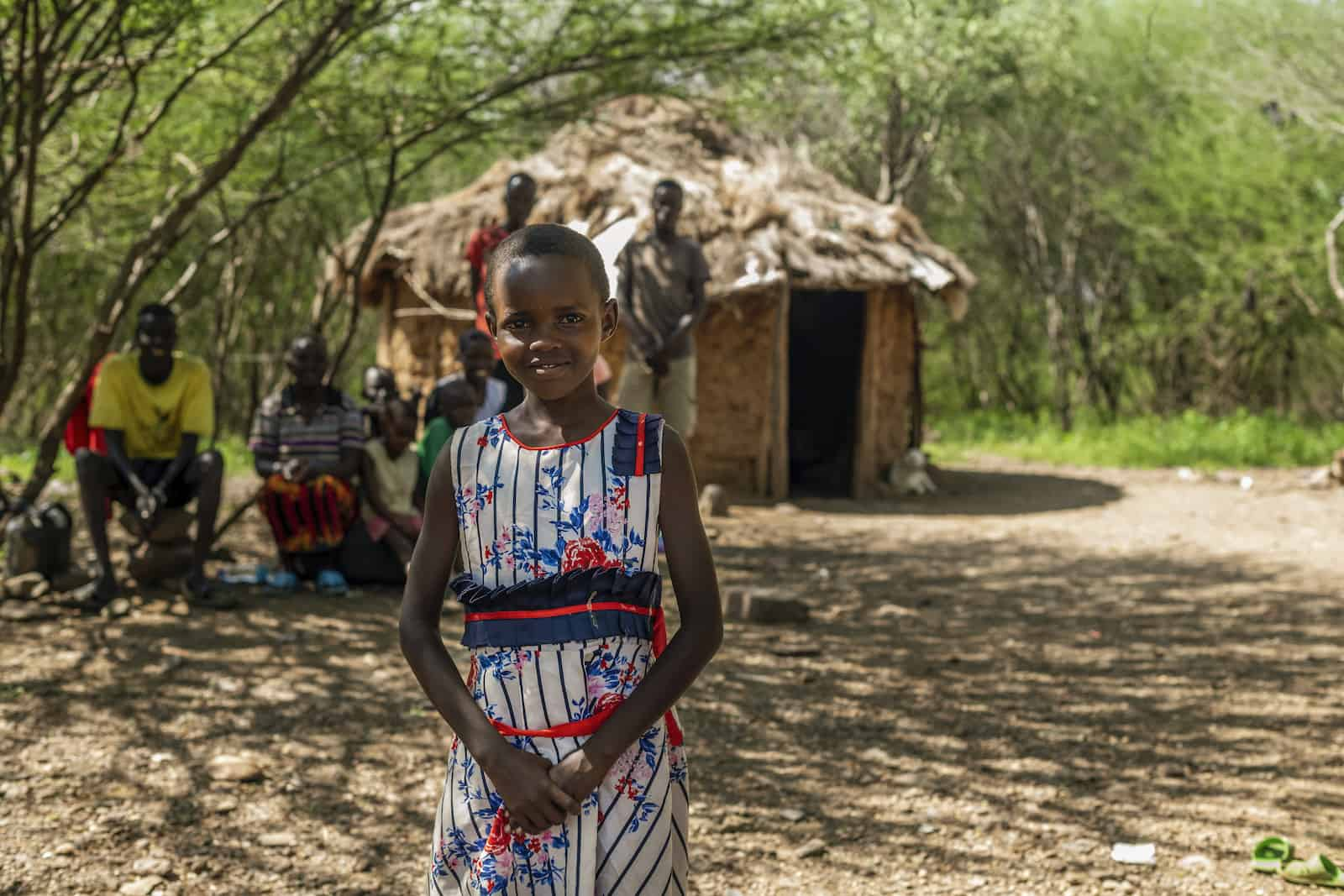 A young girl stands in front of a grass thatched hut with her family sitting behind her.