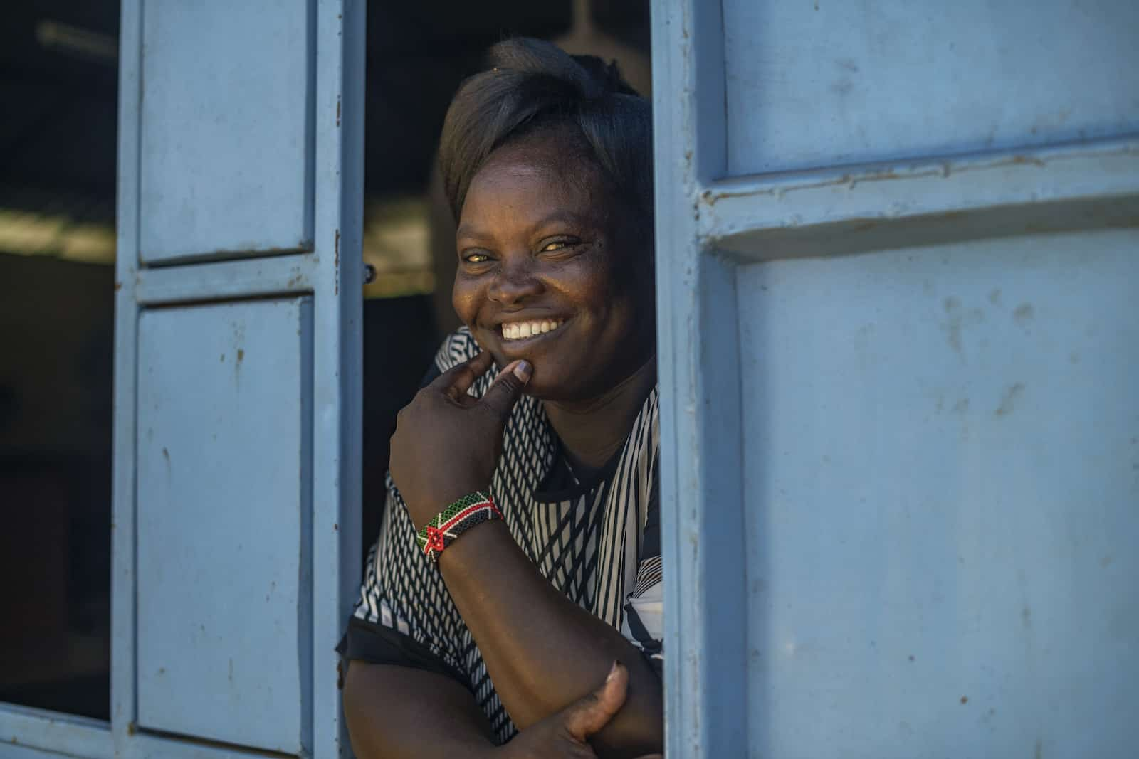 A woman who is a crusader against FGM leans out of a window with blue shutters.