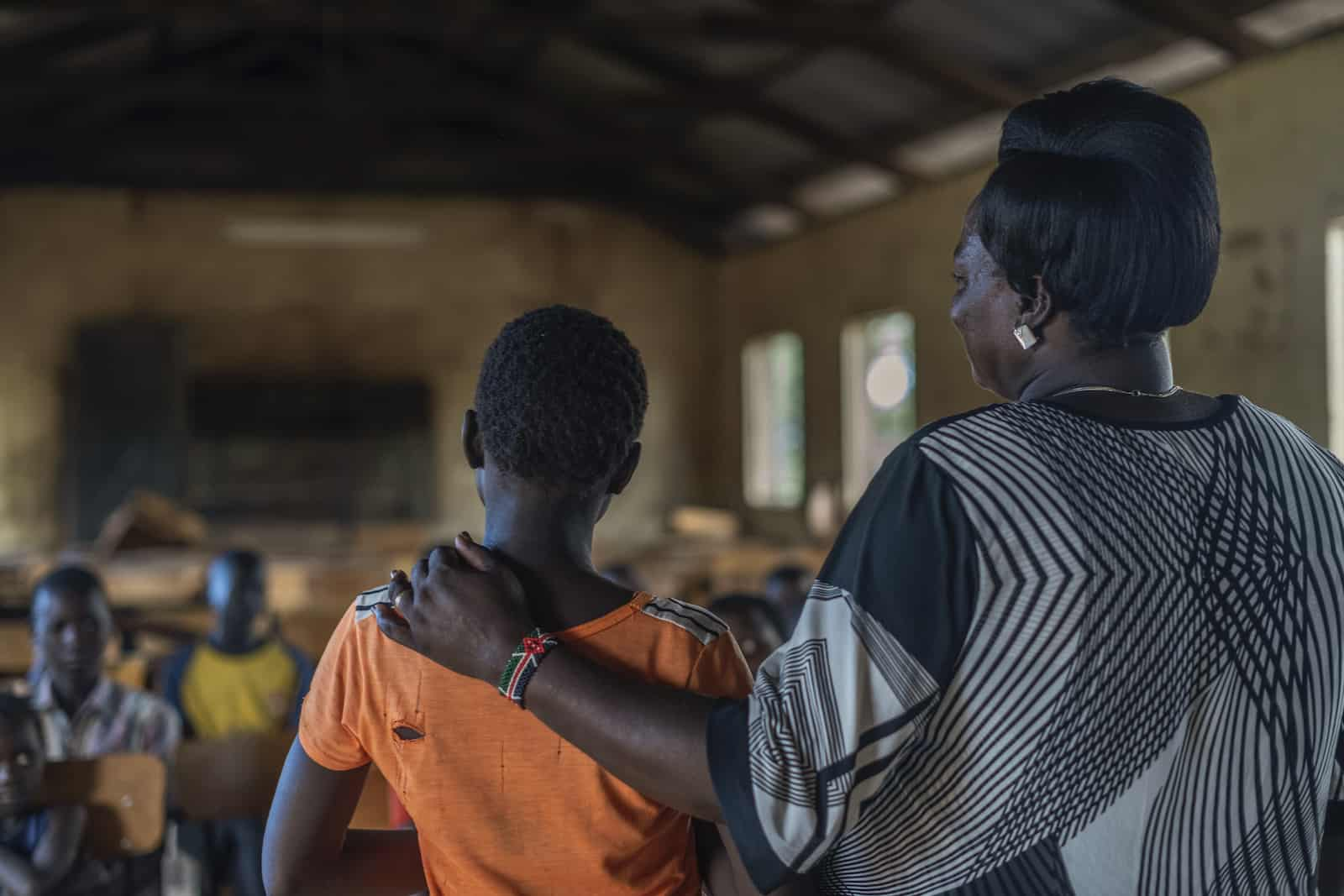 A picture from behind of a woman standing with her arm around a girl.