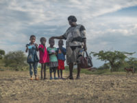 A woman stands next to four little girls.