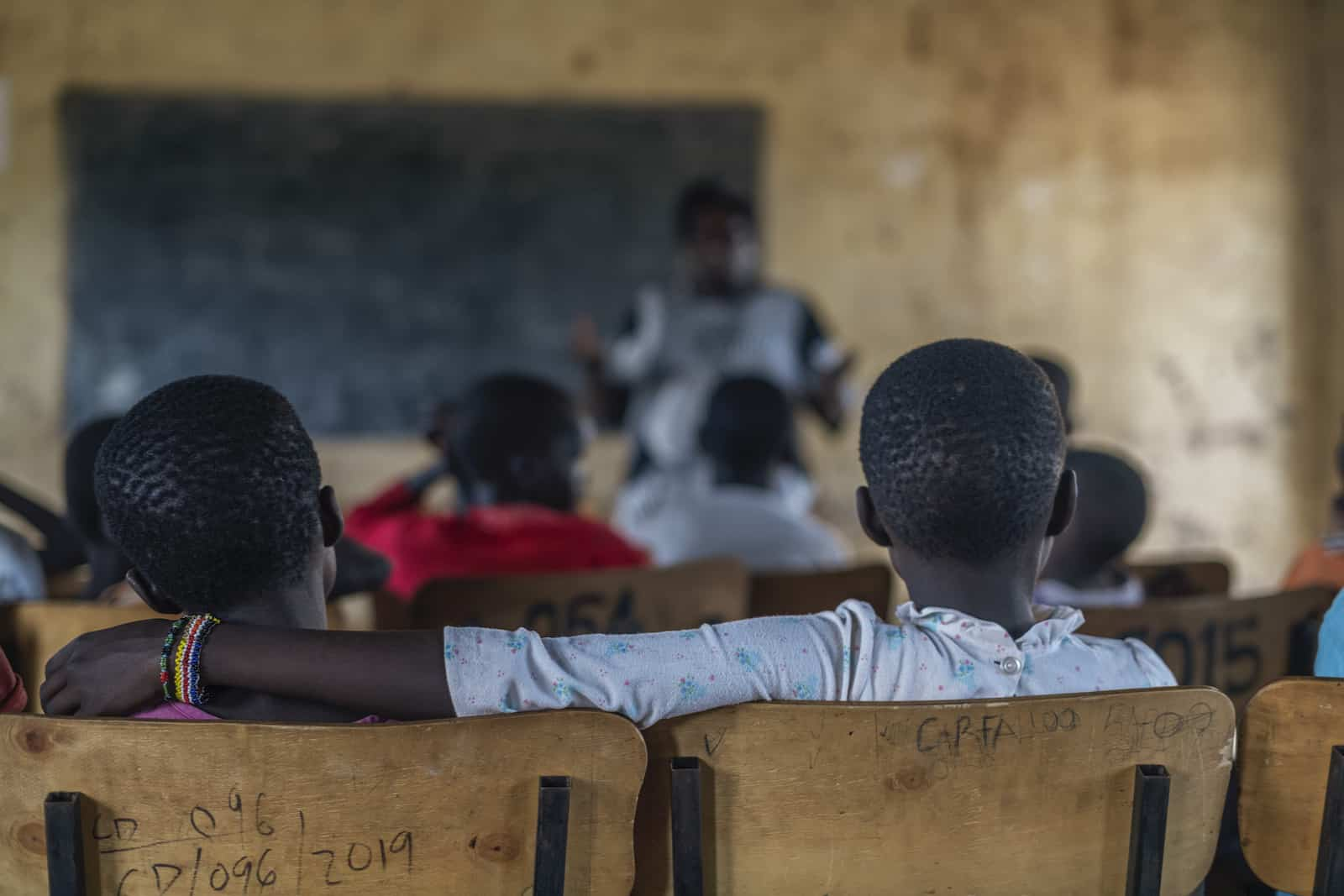Children sit in a school for girls who have escaped FGM, listening to a woman standing in front of the class.