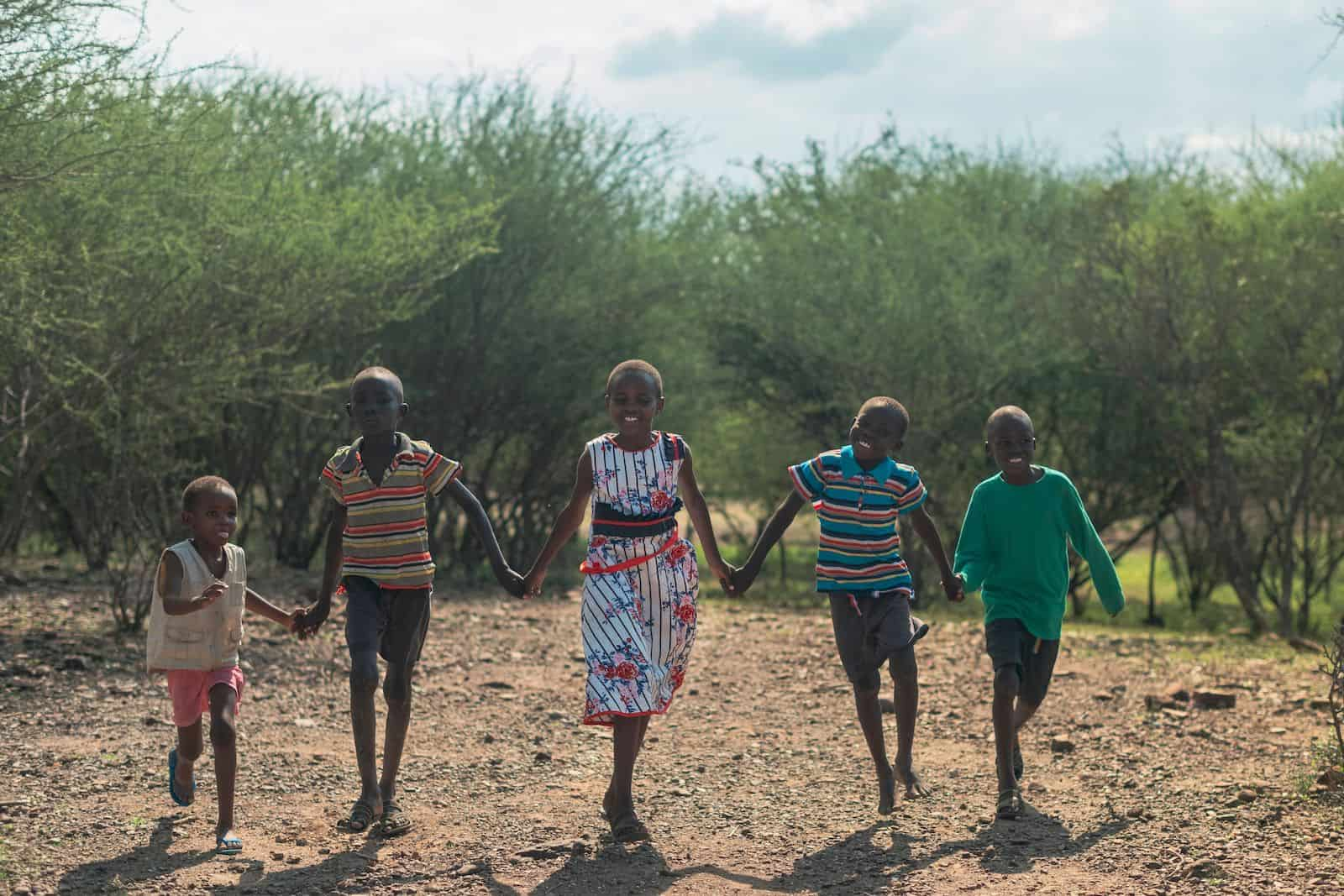 A group of five children hold hands and run towards the camera.