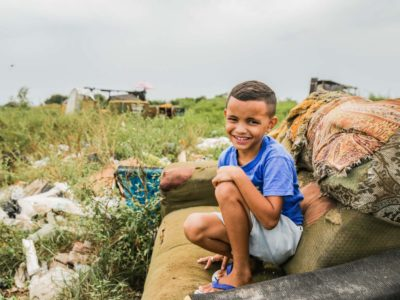 A boy sits on an old sofa in a garbage dump.