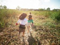 Three children run in a field wearing traditional Peruvian clothing.