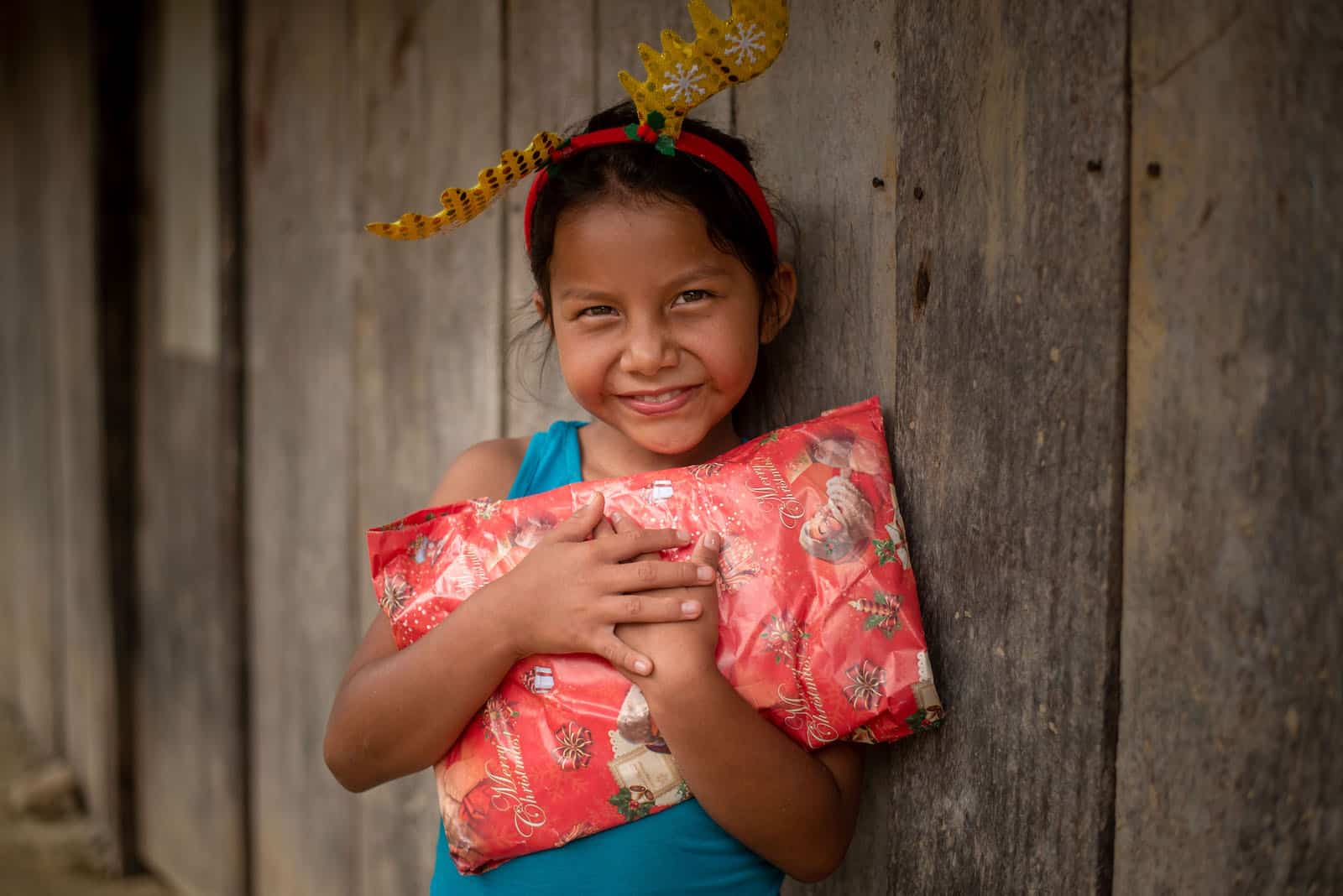 A little girl in Peru hugs a Christmas gift.