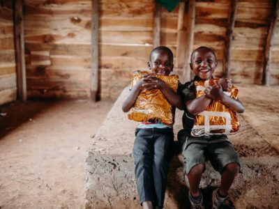 Two boys in Uganda hug Christmas gifts.