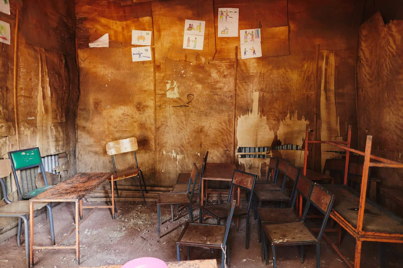 A classroom with dirt floors, plywood walls and cramped chairs.