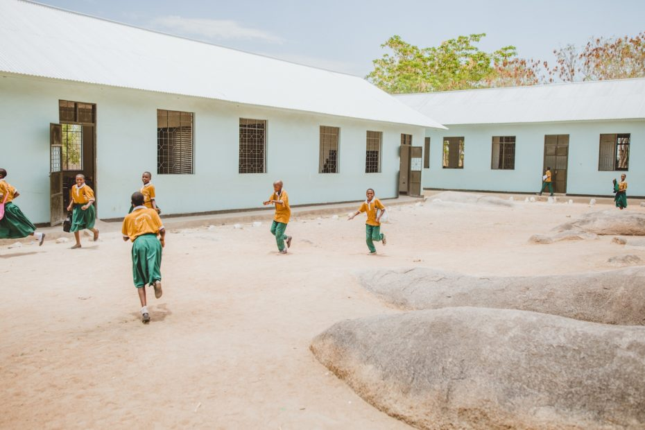 Students run and play in a courtyard ringed by classrooms.