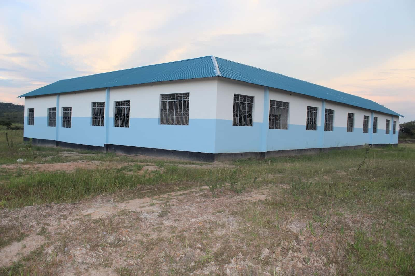 A school building with blue and white walls and windows with wrought iron bars.