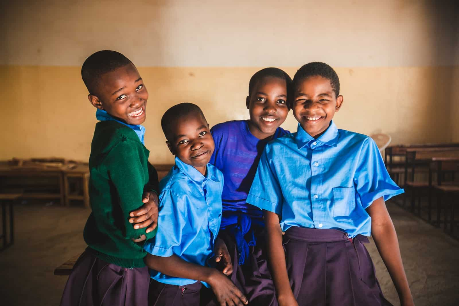 Four young Tanzanian girls wearing school uniforms smile at the camera.