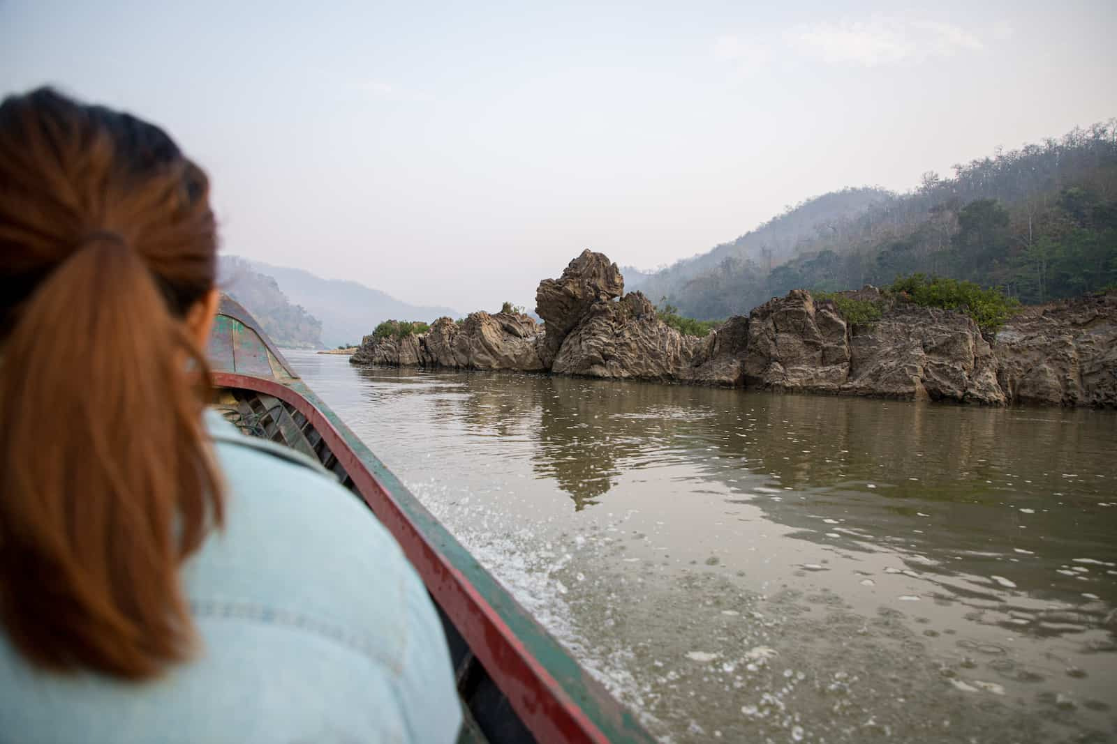 A woman rides on a canoe down a river surrounded by rocks and mountains.