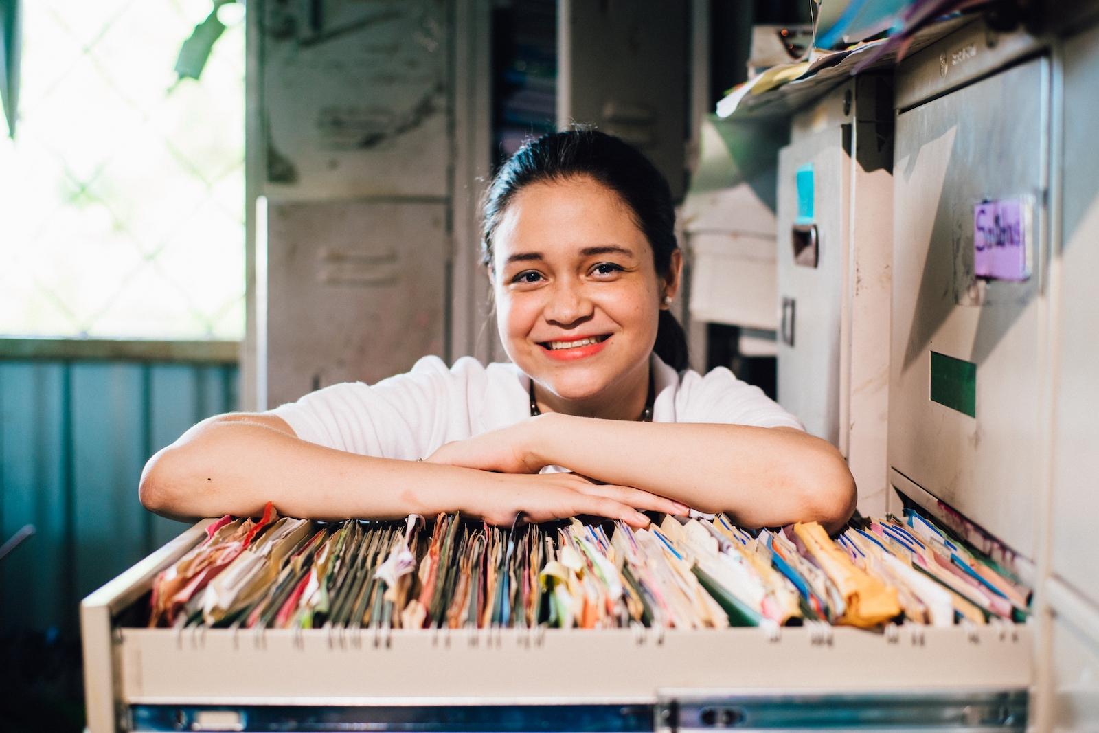 A woman leans on a drawer of file folders, smiling, showing the relation between poverty and research.