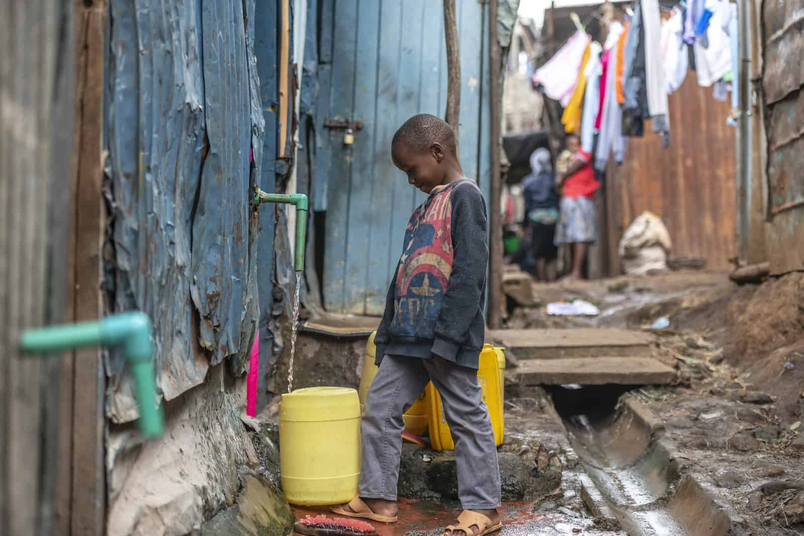 A boy stands in an alley filling a water jug at a tap.
